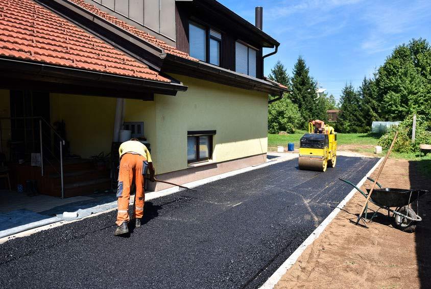 Workings paving asphalt driveway of Pinellas County home